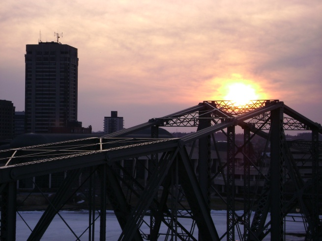 The sun setting over the Alexandra Bridge and Gatineau